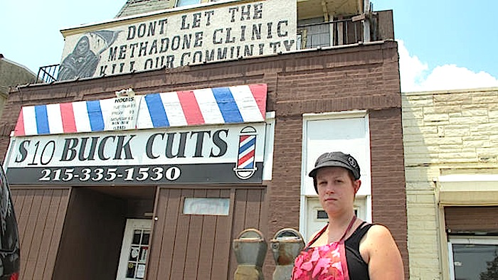The owner of $10 Buck Cuts protests the planned methadone clinic next door. Photo via