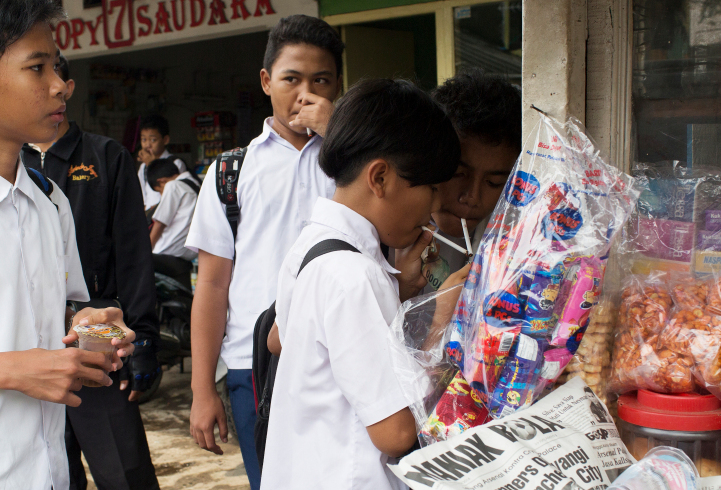 Kids buy single cigarettes and light them at a kiosk after school in Jakarta. Kiosks like this, which don't ask for age ID, are often in close proximity to schools.