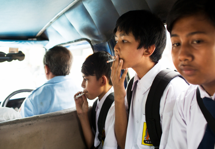 Children smoke on a bus home from school in Jakarta. There are smoking regulations in many public places but little enforcement.