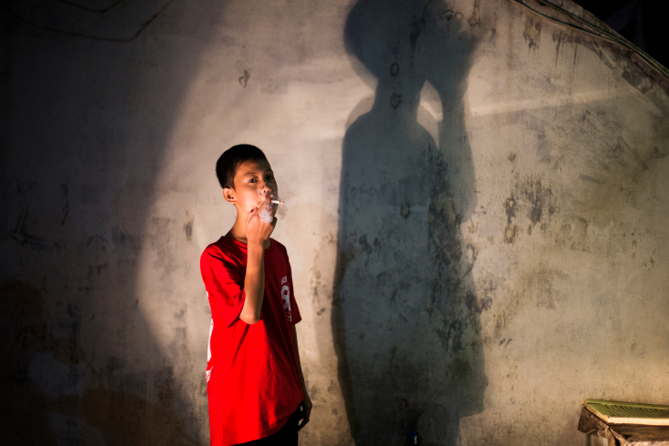 Andika Prasetyo, who smokes about a pack a day, outside an internet cafe in Depok, West Java.