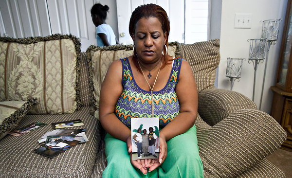 Stephanie George holds up a picture of her children, which includes her youngest son Will, who was shot dead months before she was released. Image Via