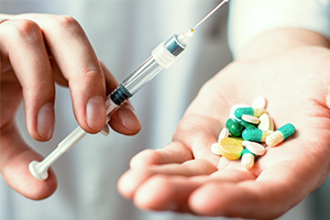 substance-shutter319467206-syringe-and-pills-in-hand