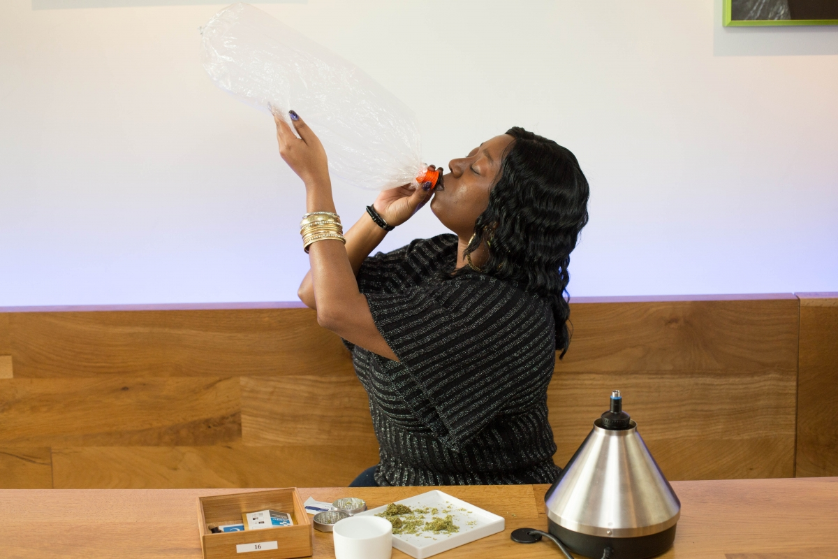 """Younger African American woman inhaling vaporized cannabis in a dispensary"" Sonya Yruel/Drug Policy Alliance"