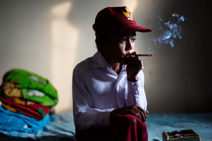 Ilham Hadi, a third-grader who has smoked up to two packs a day since he was four, in his bedroom in Sukabumi.