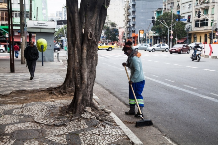 A woman sweeps the streets of downtown São Paulo as part of her few hours of daily work.