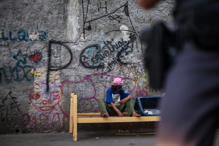 A program participant sits on a bench while a police officer patrols the area. Most participants in the program don't face threat of arrest. Photo via