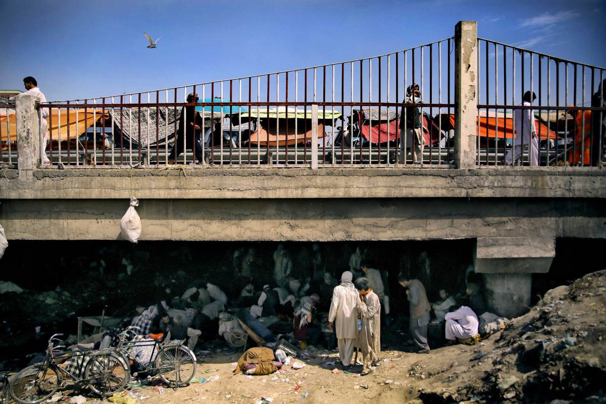 A view of Pul-e Sukhta bridge from the banks of the dried Kabul river. While hundreds often thousands of addicts swarm below in a self-fueling network of drugs, crime and despair, life seems to continue unaffected above.